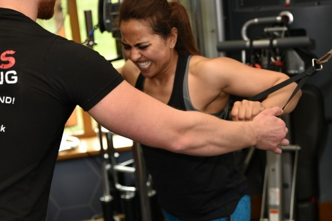 female personal training client with a male personal trainer: she's doing a chest press with a cable machine